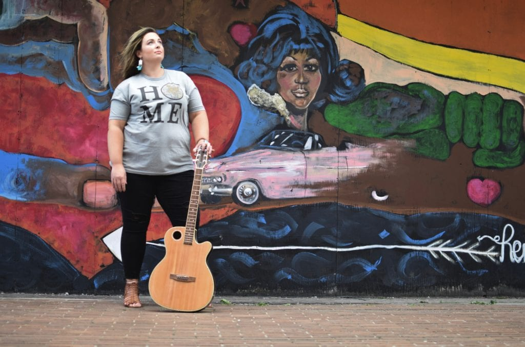 Carissa with her guitar in front of the Sabrina Nelson Mural on Woodard