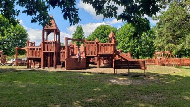 castle-themed wooden playground at Bay Court Park in Independence Township